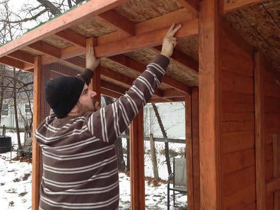 Matt installs a piece of wood for the top frame of the coop door.